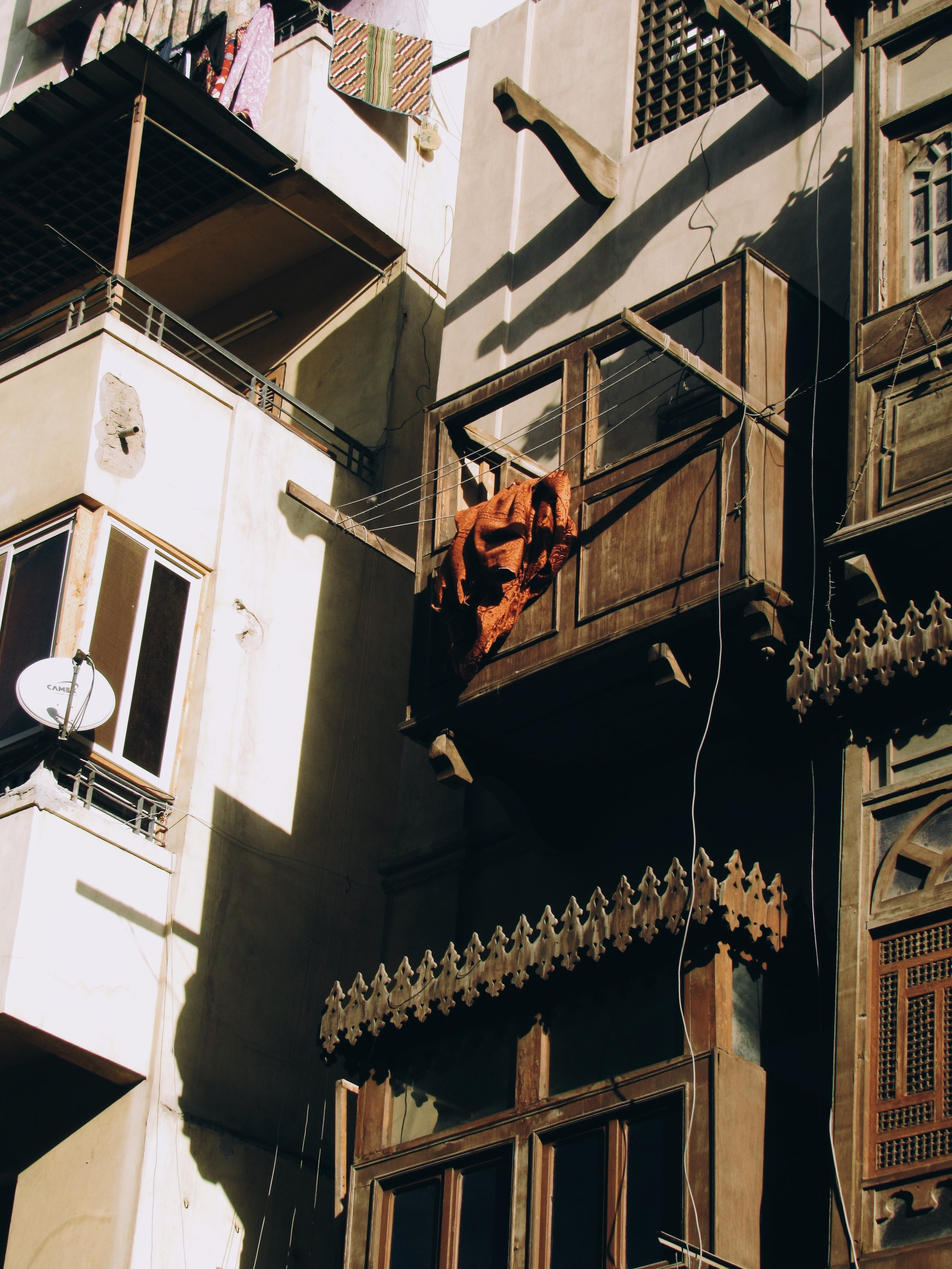Cairo Commune |  December 18, 2018 Cairo, Egypt | A burning orange cloth or garment hanging on a string-line by a window, one of many among dwellings beside Khan al-Khalili in Downtown Cairo.