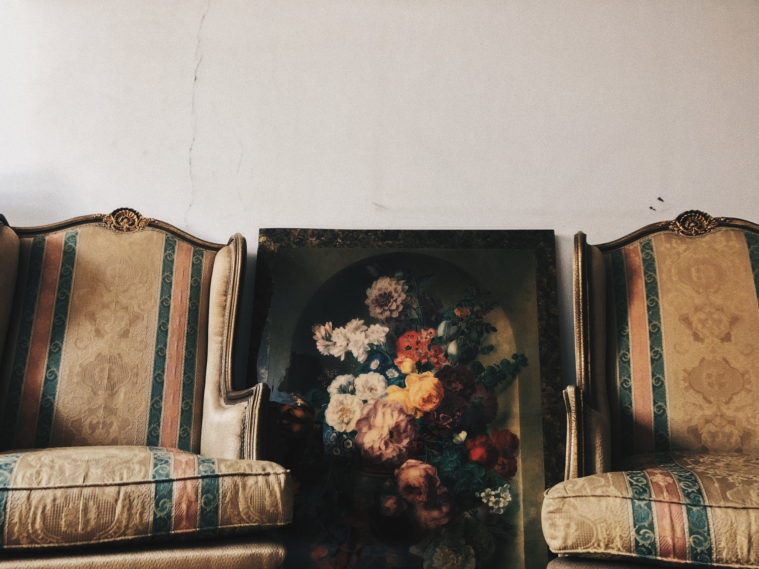 A Dwelling Place |  July 28, 2018 Port Fou'ad, Egypt | A still life painting of a flower bouquet resting against the wall and in between two arm chairs in the living room.