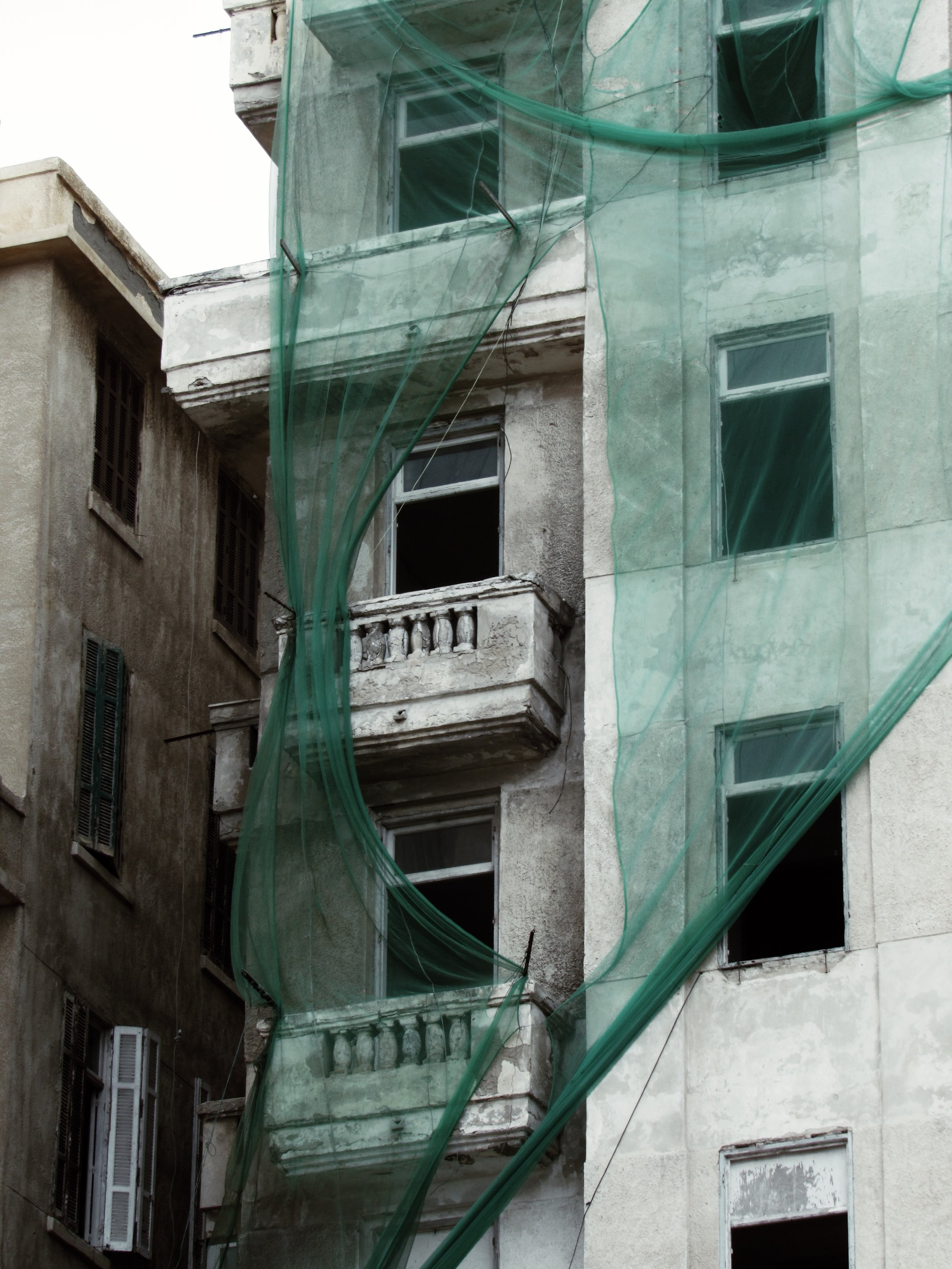 Apartment on Main Street |  December 19, 2018 Alexandria, Egypt | An aged tall apartment building oddly draped by a green thin fabric.