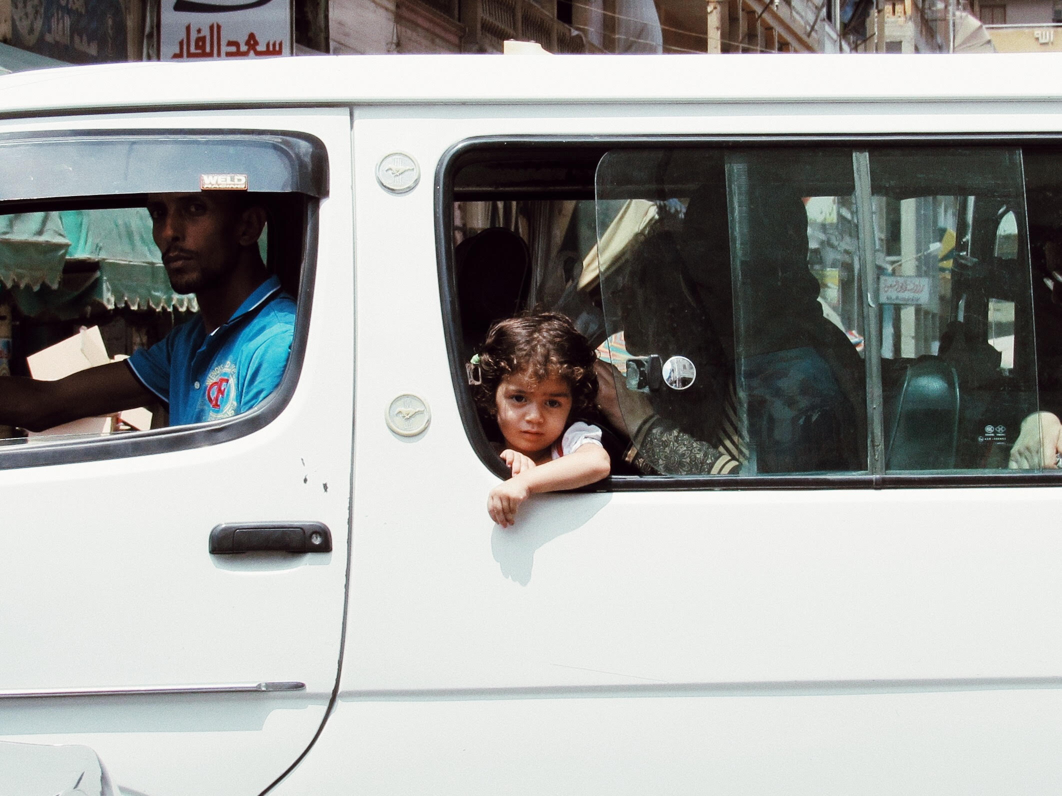A Girl in Bus |  July 28, 2018 Port Said, Egypt | A young girl, irritated by the Summer heat, reaches out of the crowded white micro-bus for space.