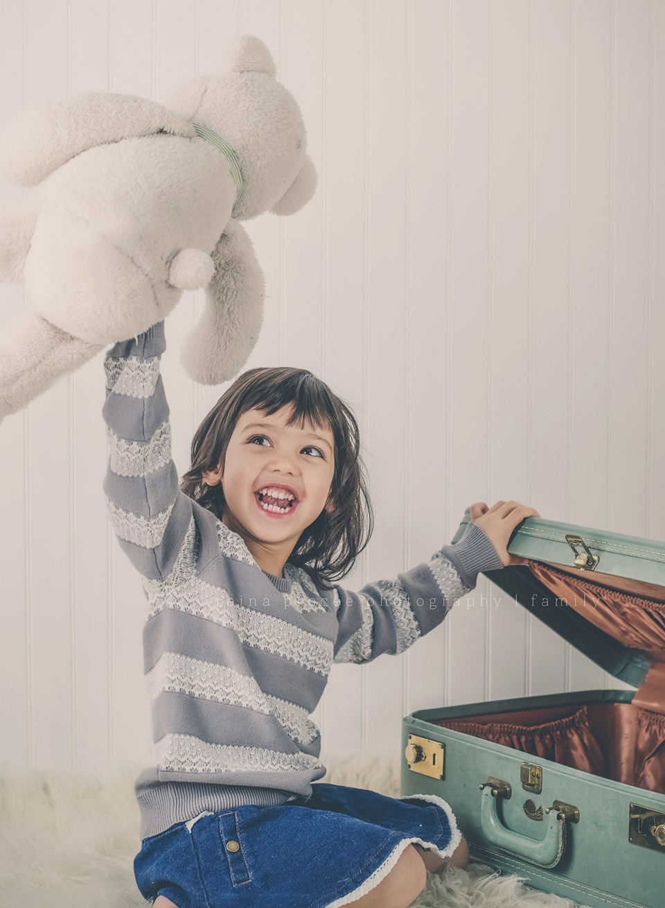 little girl playing with teddy bear and green vintage suitcase