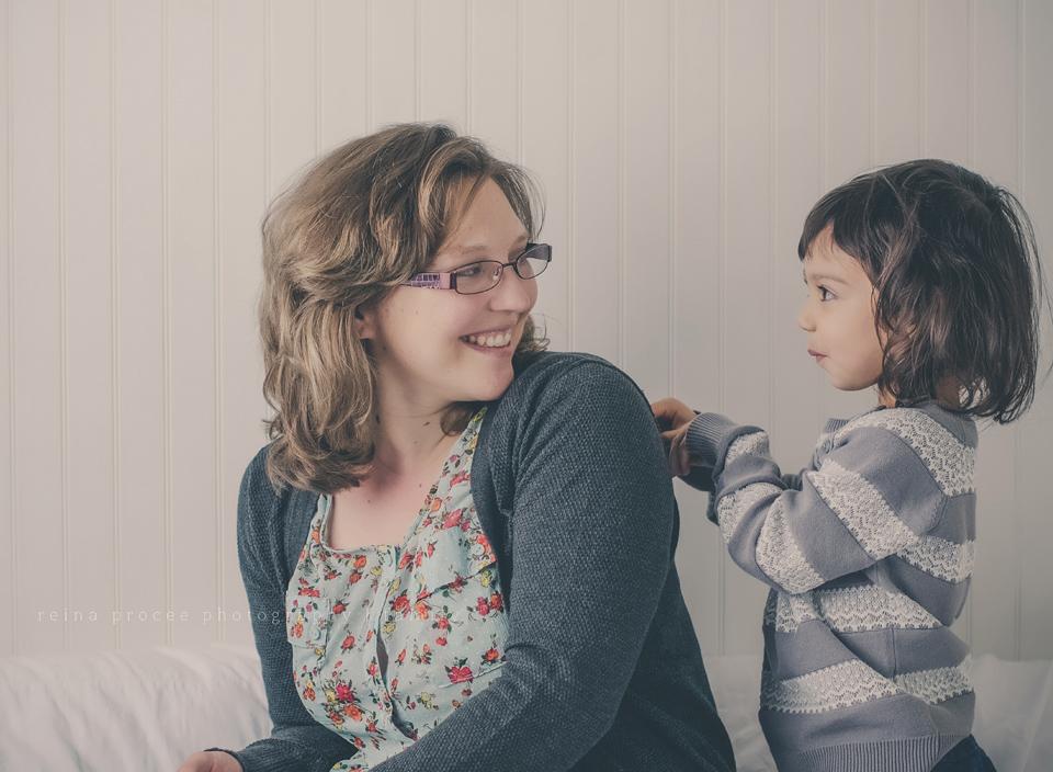 little girl tickling mother