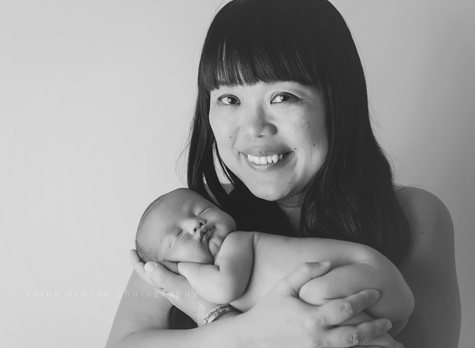 mother smiling while holding baby boy