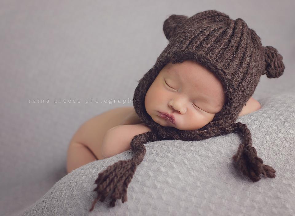 baby boy sleeping on grey blanket with brown bear hat
