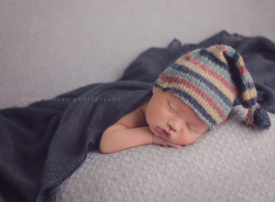 baby boy sleeping on grey blanket with navy blue blanket and stripped hat