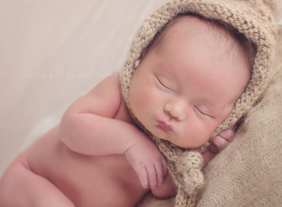 baby boy sleeping with a brown bonnet