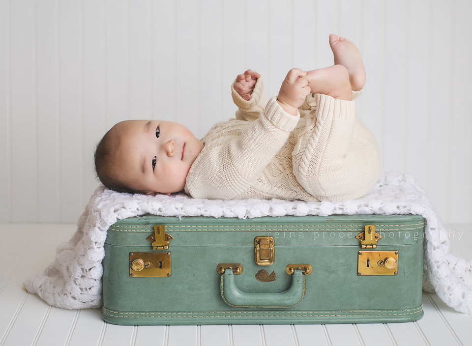 baby lying on green vintage suitcase holding his feet