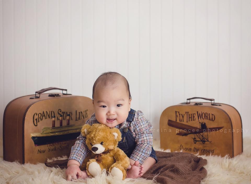 baby boy sitting between vintage suitcase holding teddy bear