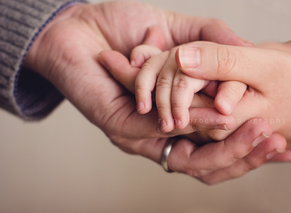 mother and father holding son's hand