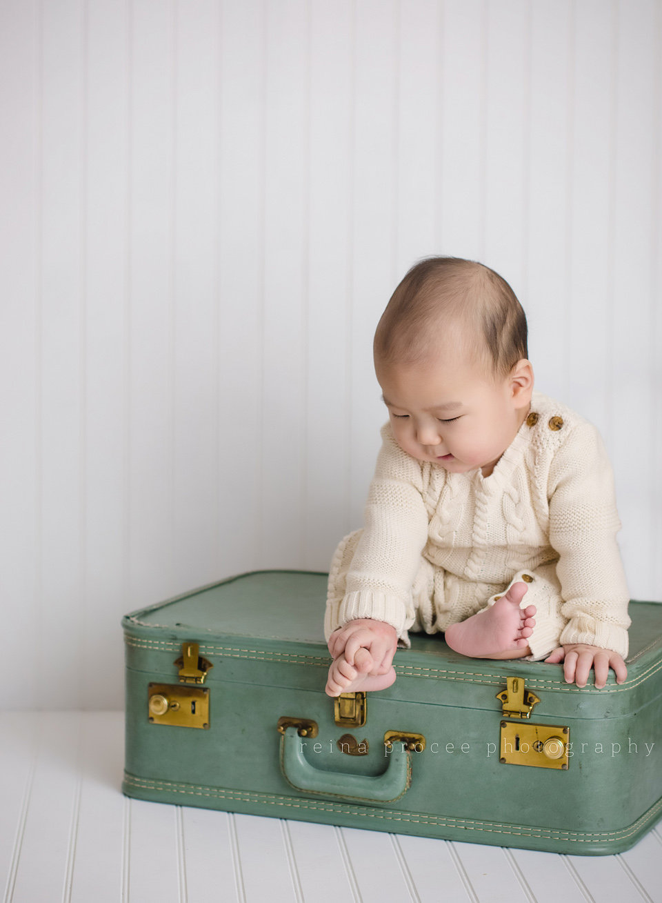 son sitting on green suitcase looking at toes
