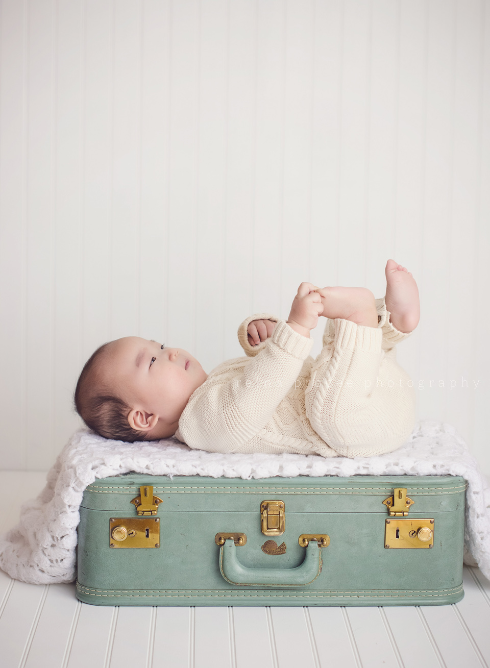 son lying on green suitcase playing with toes