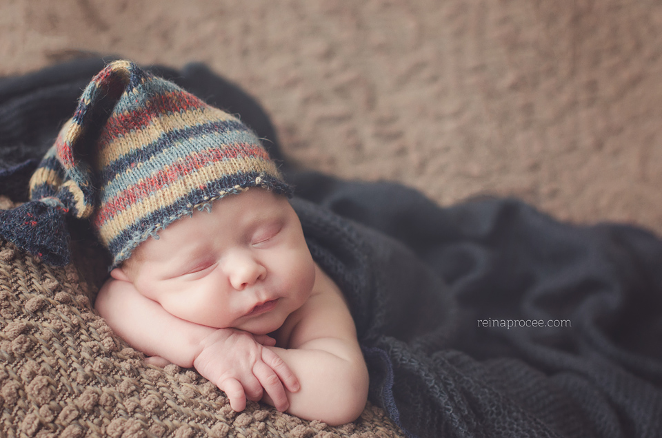 newborn baby lying on brown blanket with navy blue blanket and brown and navy blue hat