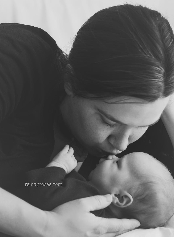 mom kissing newborn baby son