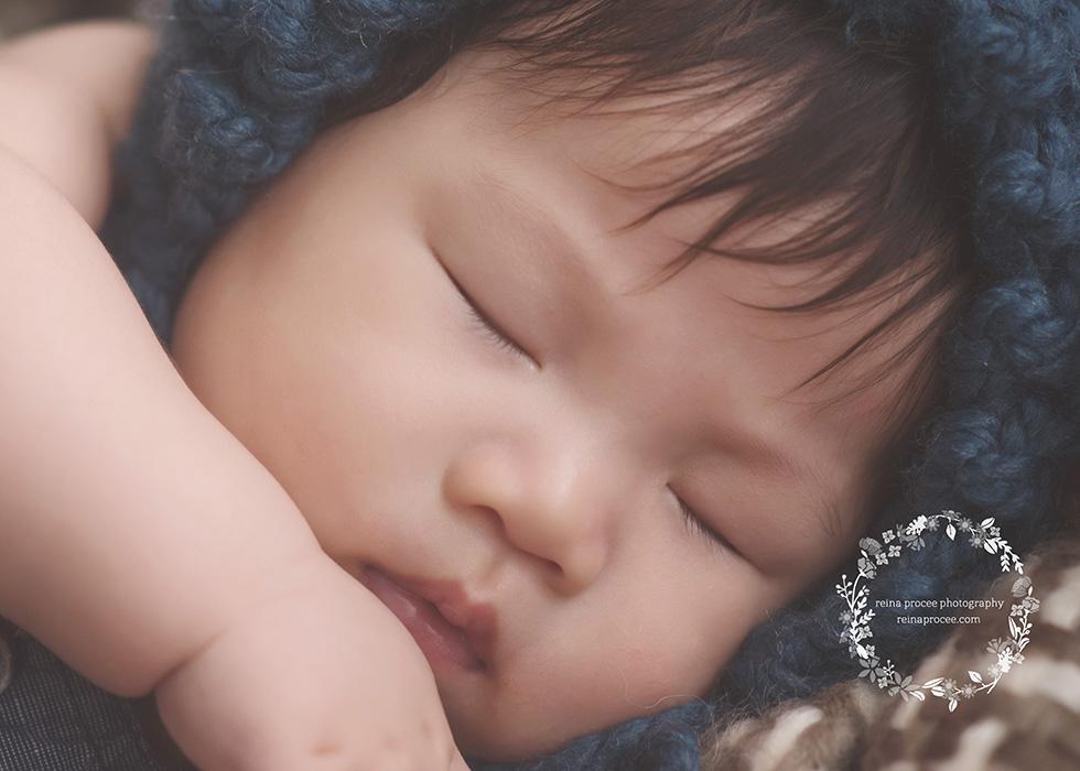 baby boy with a blue bonnet sleeping