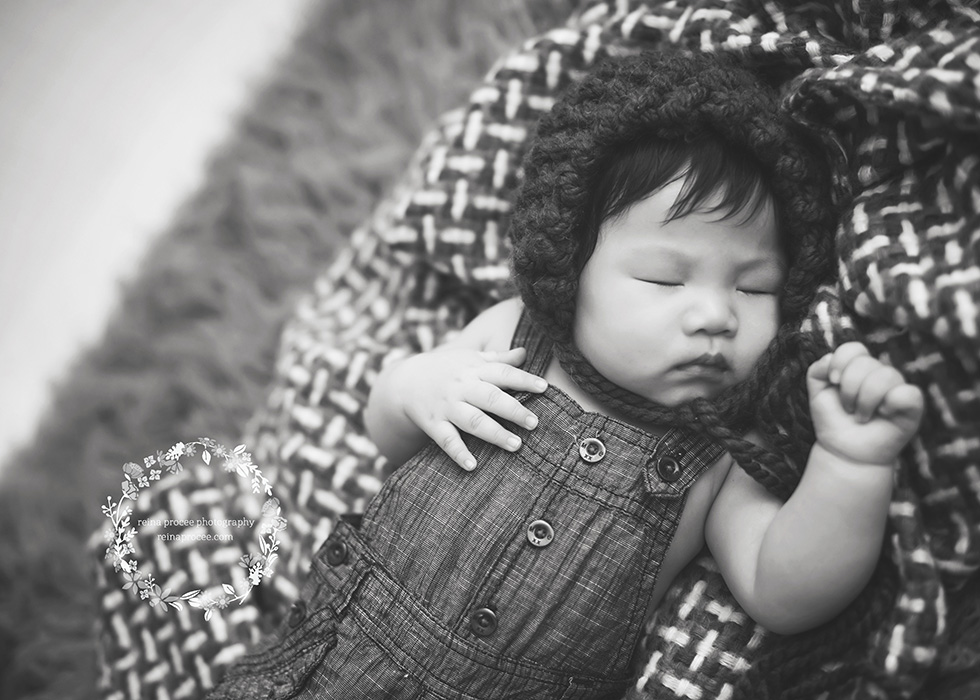 baby boy sleeping on a rug with a bonnet in black and white