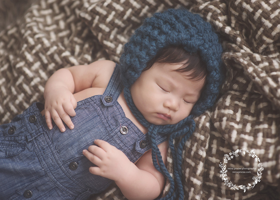baby boy sleeping wearing blue overalls and blue bonnet