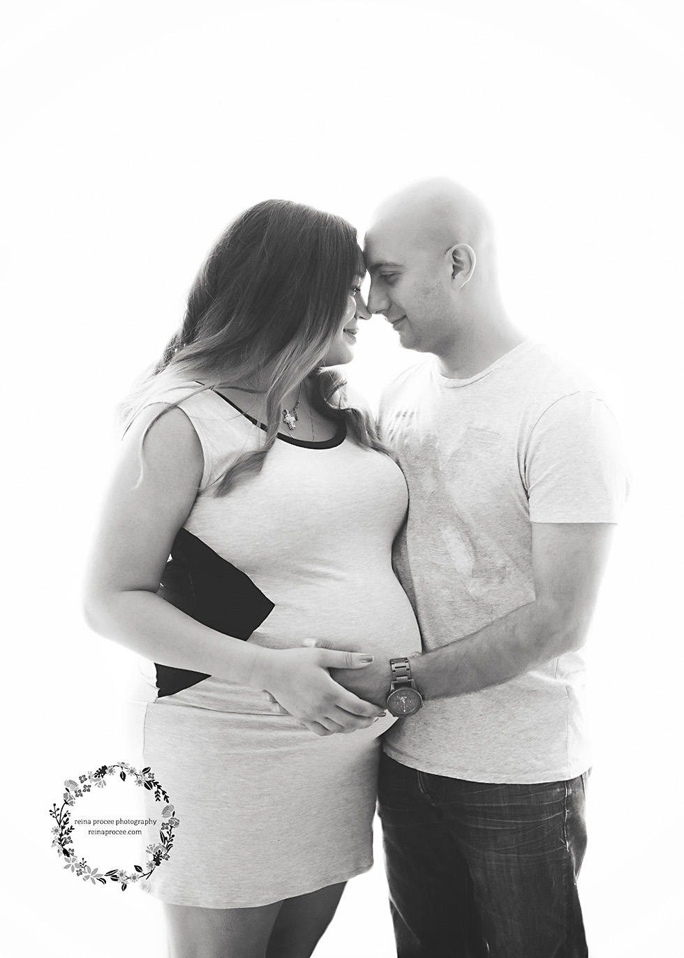 mom and dad hugging and holding pregnant belly in black and white