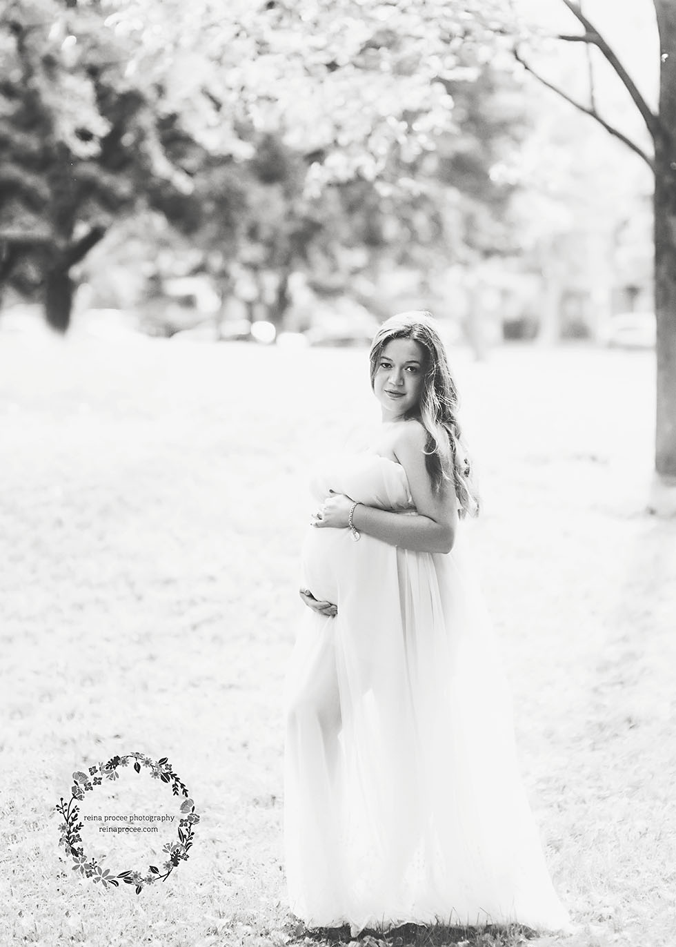 pregnant woman hugging her belly in a field with a cream dress blowing in the wind in black and white