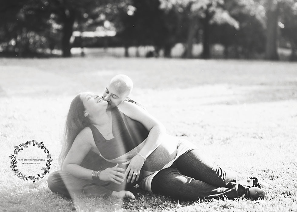 mom and dad sitting in field hugging and kissing in black and white