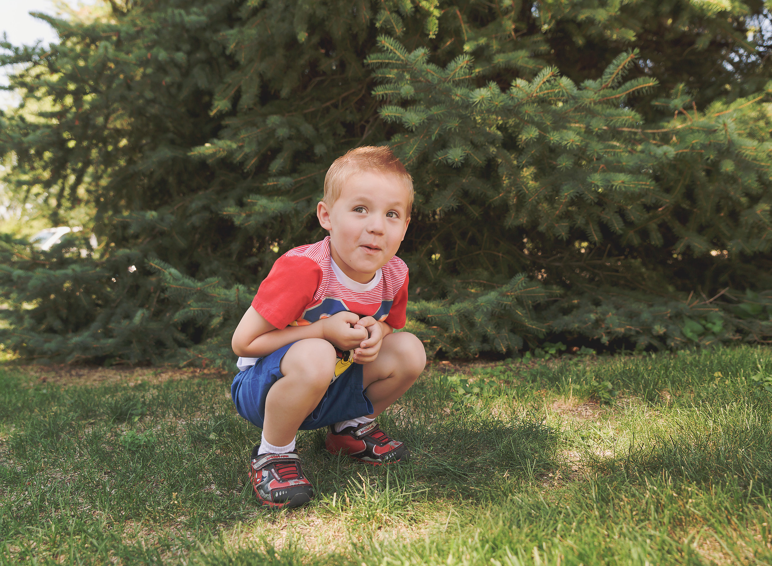 Dear Me Photography Bismarck ND little child crouching by pine tree