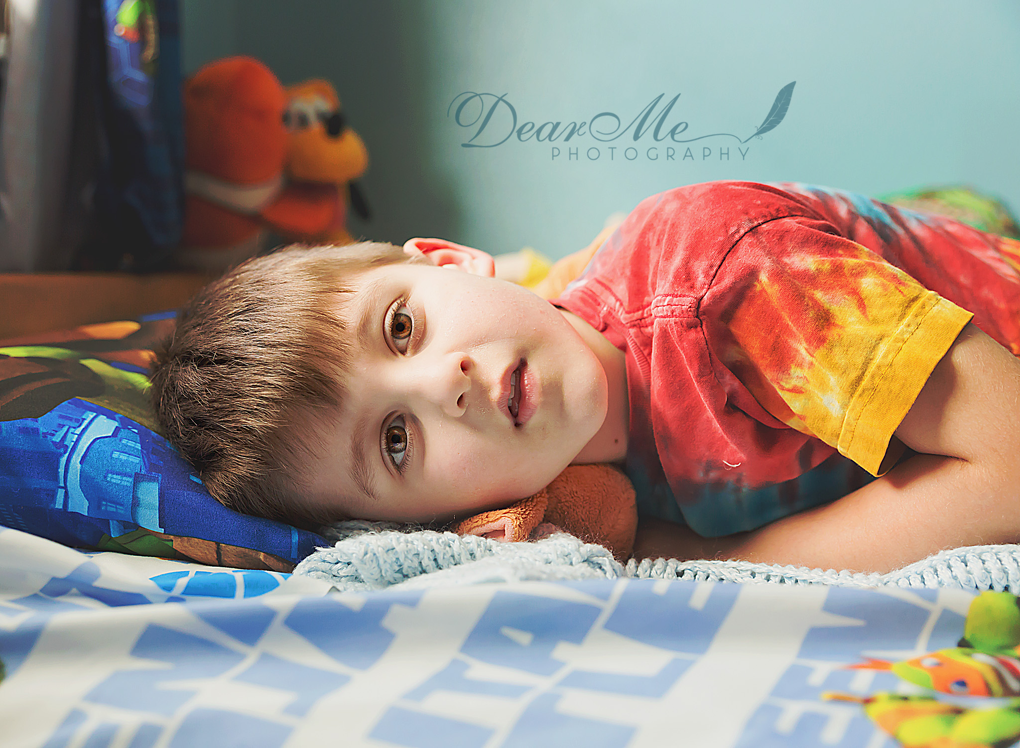 dear me photography bismarck faces of autism young boy laying down with serious expression
