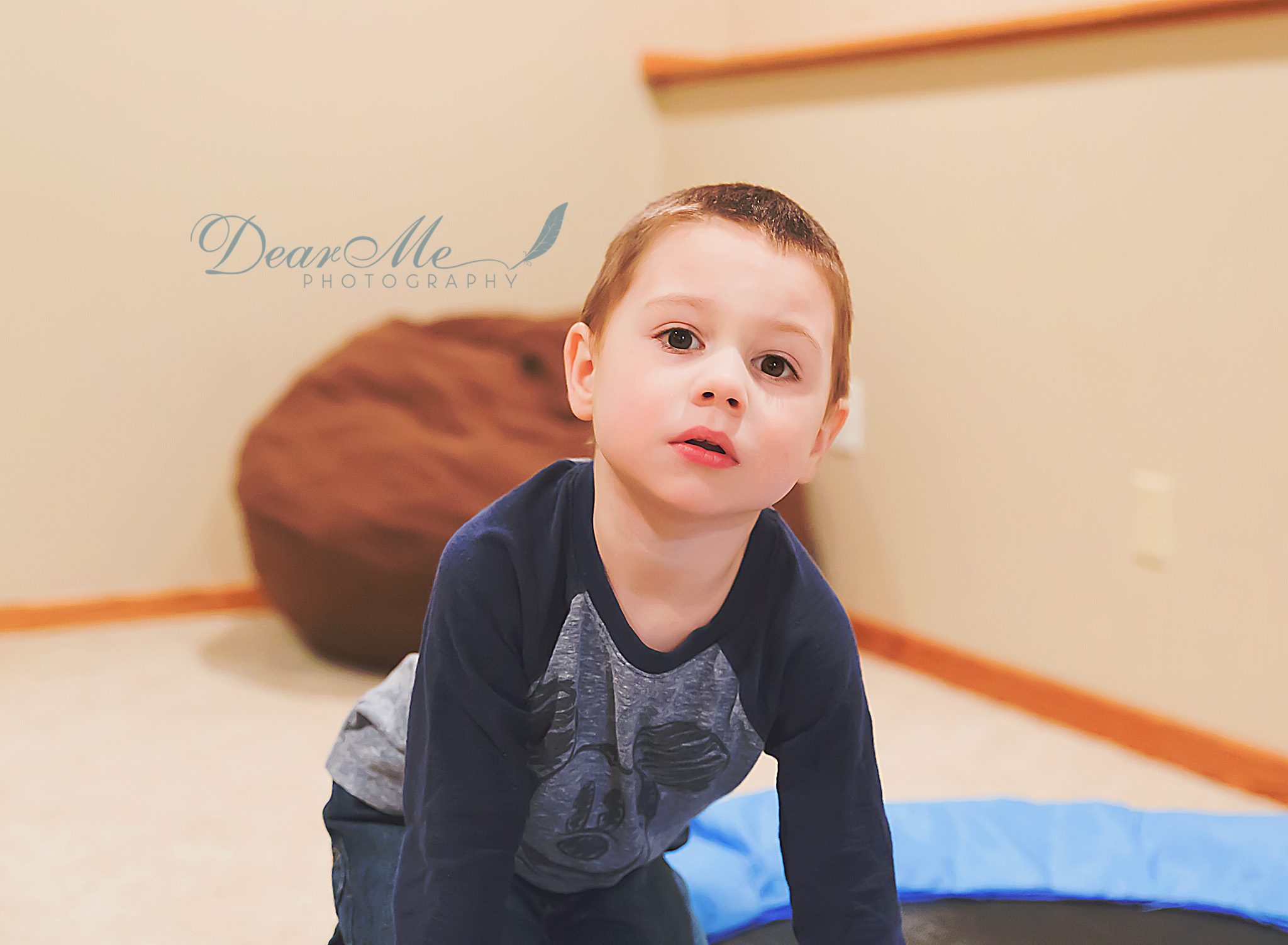 dear me photography bismarck photographer boy kneeling on indoor small trampoline