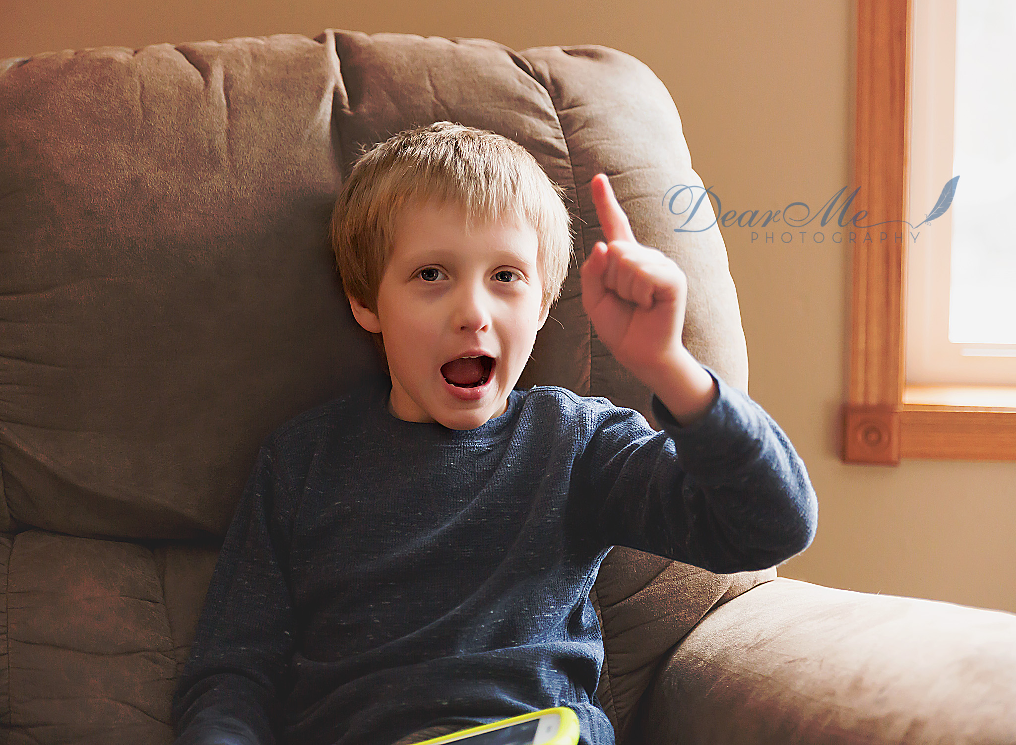 dear me photography mandan photographer  boy sitting on chair with his finger up in the air