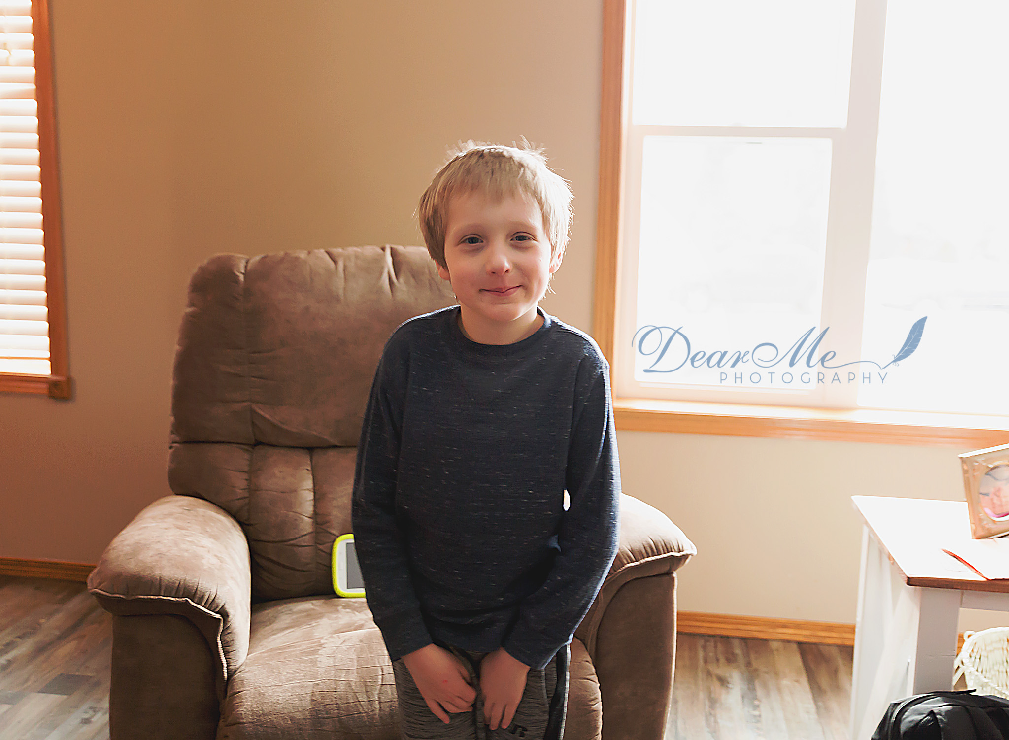 dear me photography mandan photographer boy standing in living room with hands in lap