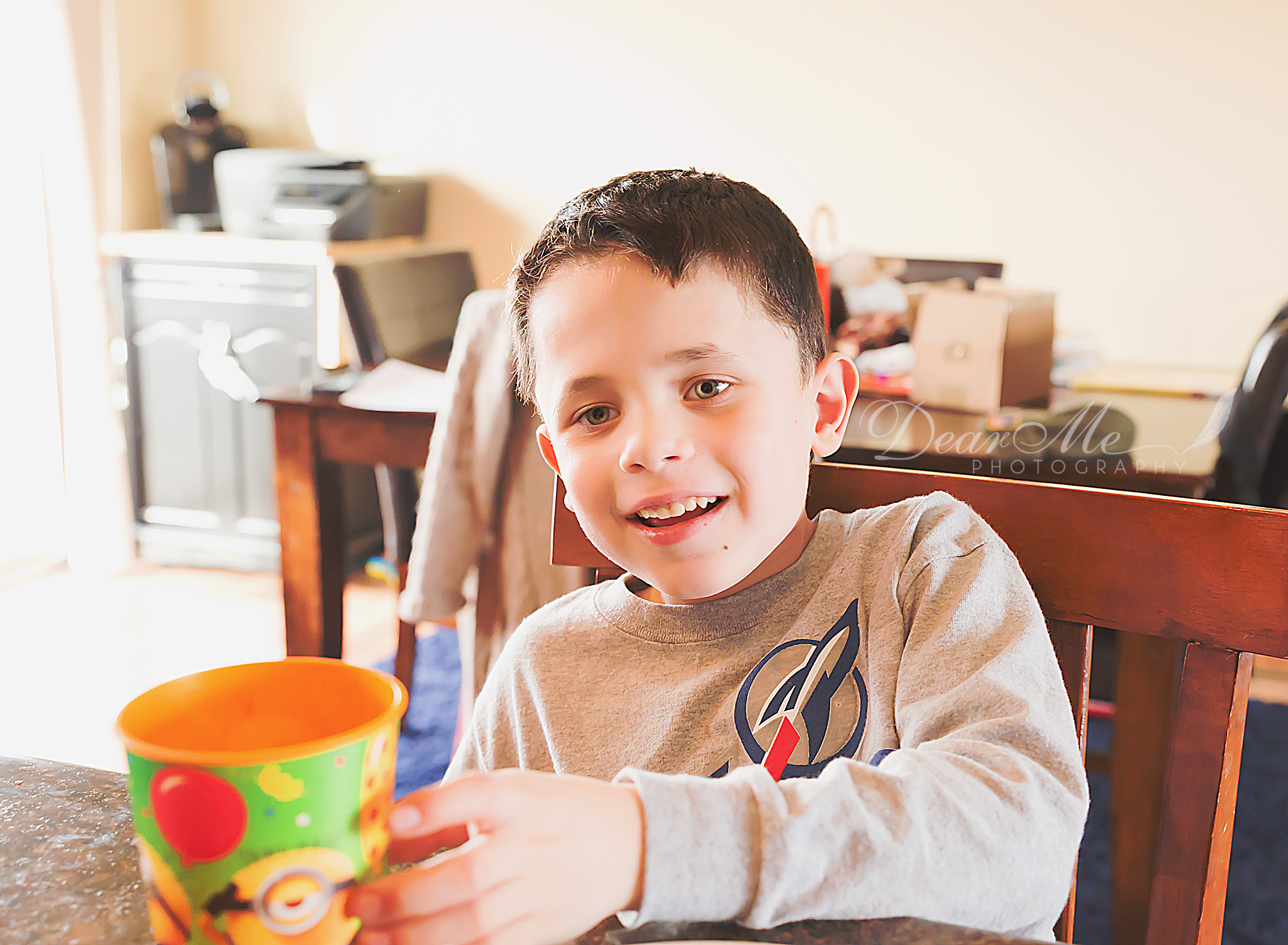 dear me photography bismarck photographer boy smiling reaching out for a cup
