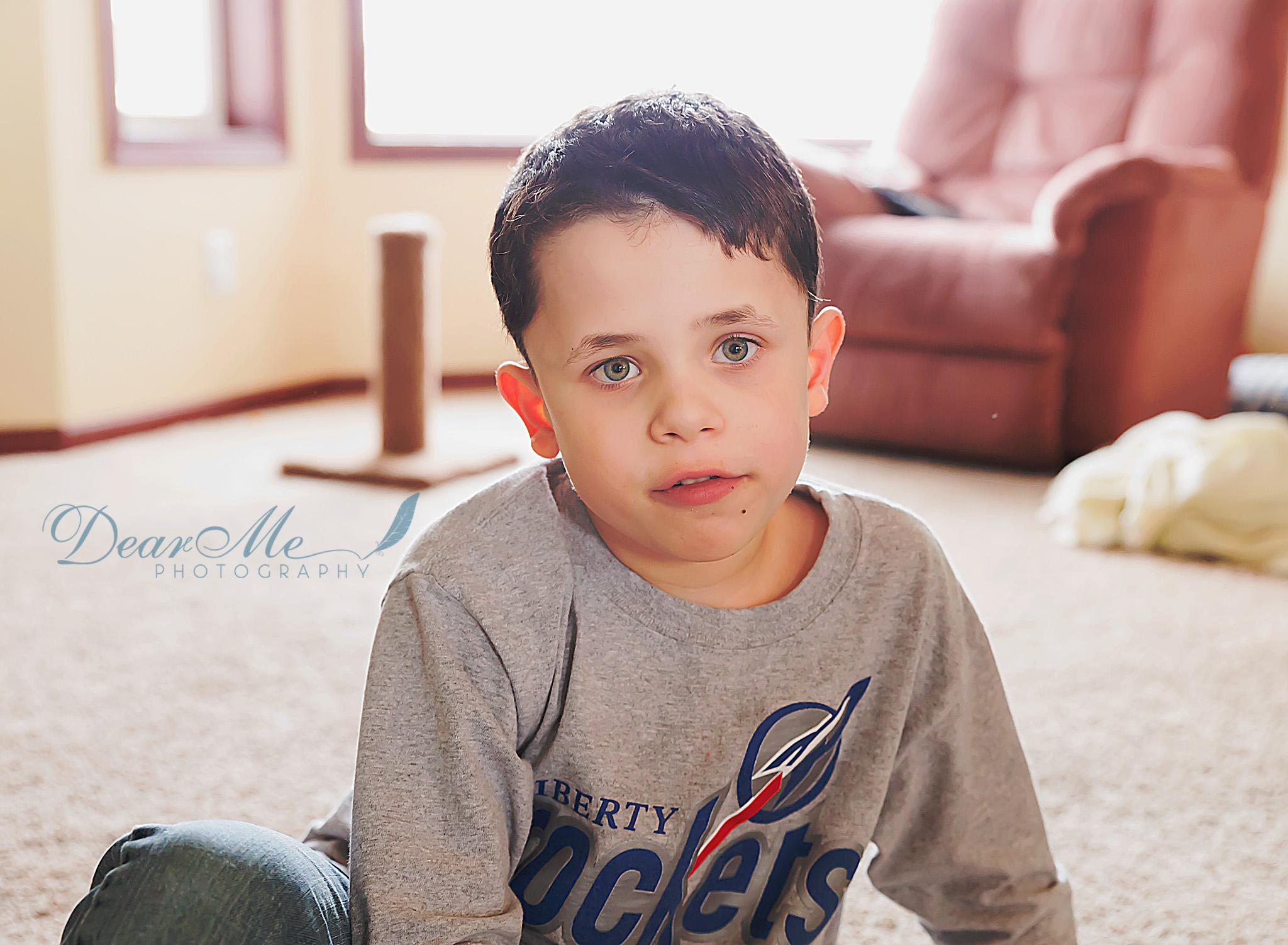 dear me photography bismarck photographer boy in grey shirt sitting on living room floor
