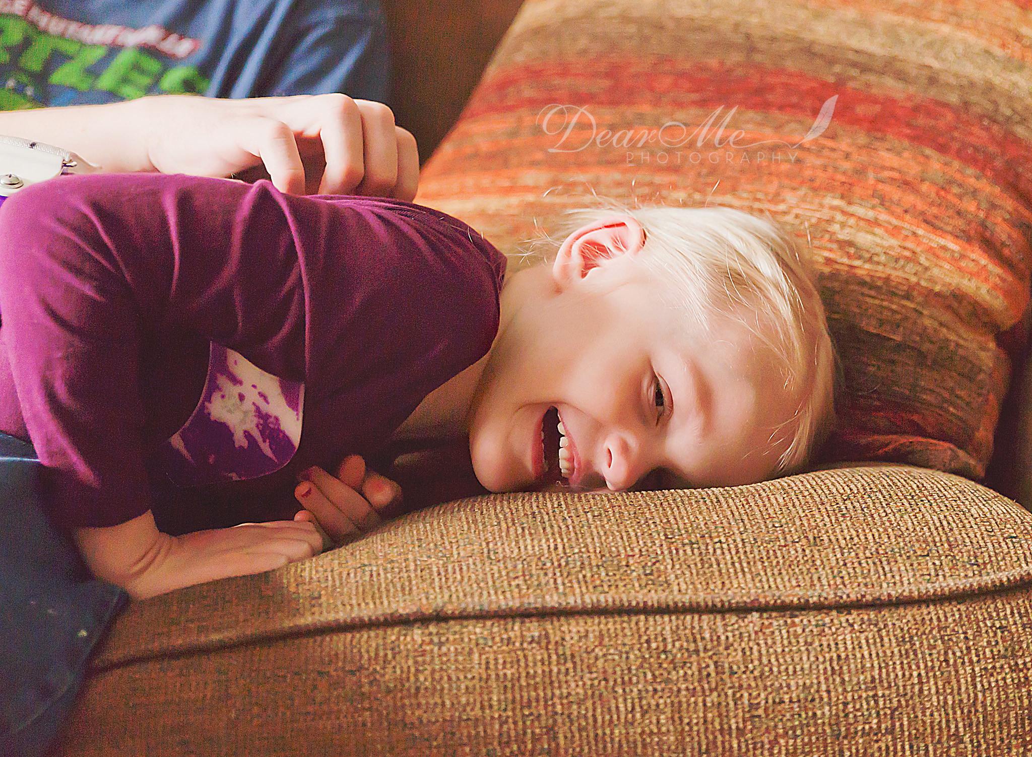 dear me photography mandan photographer girl laying on couch laughing