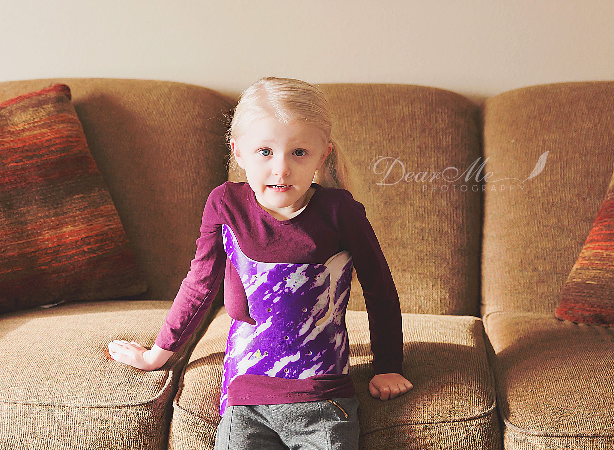 dear me photography mandan photographer girl sitting on brown couch with purple long sleeve shirt