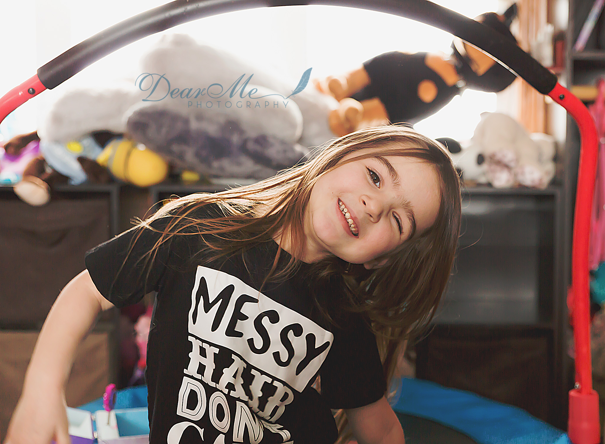 dear me photography mandan photographer little girl winking with head tilted to the side