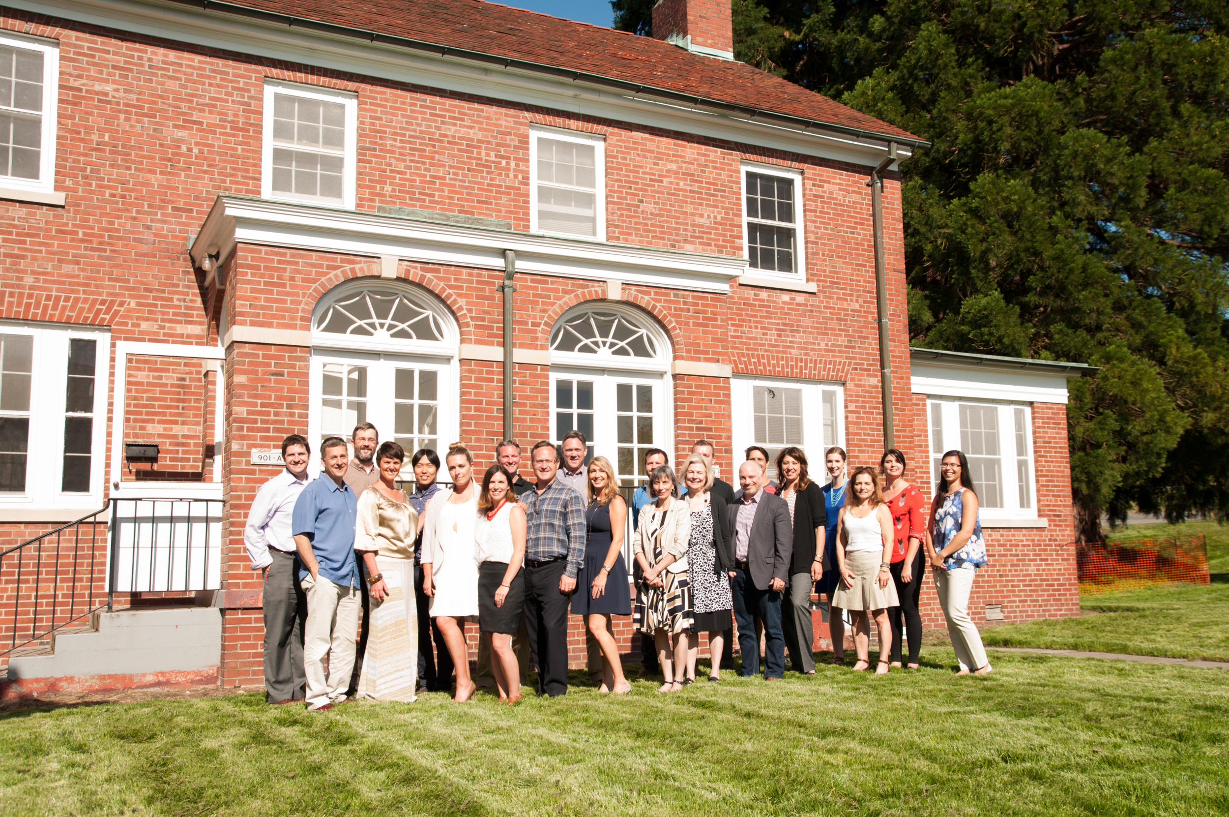 PICTURED ABOVE:    The design, development, marketing and sales team for Fort Lawton stand in front of one of the Scheuerman plan homes prior to restoration.