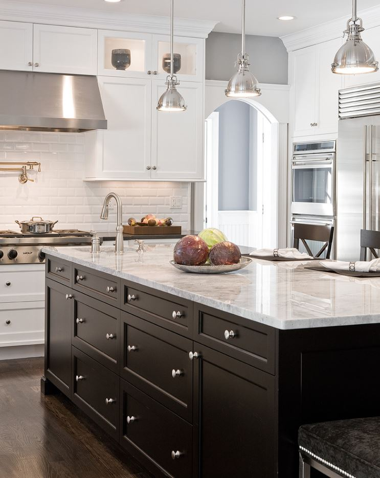 Polished quartz slab countertops over two-tone custom designer cabinetry in kitchens