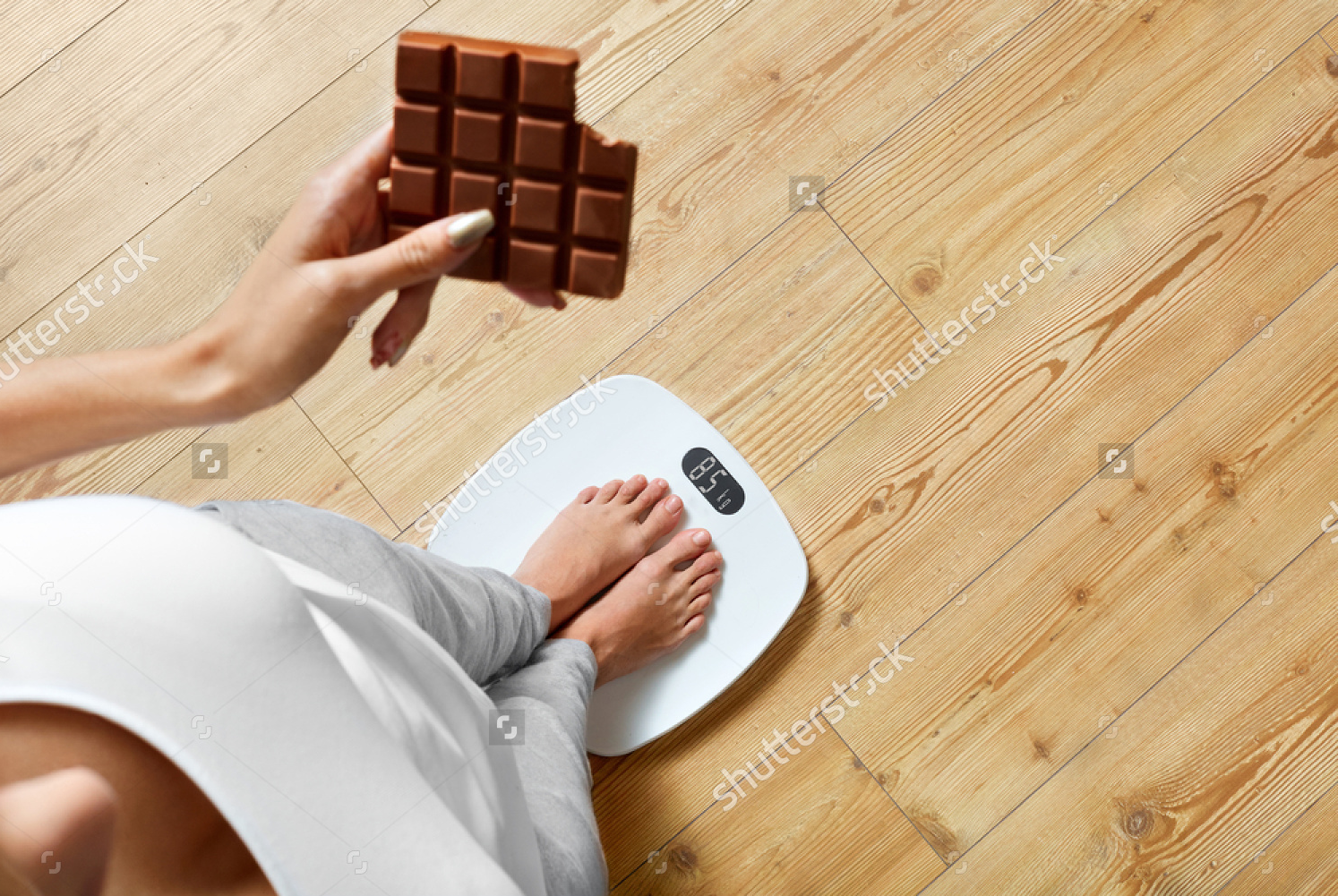 stock-photo-diet-young-woman-standing-on-weighing-scale-and-holding-chocolate-bar-sweets-are-unhealthy-junk-345851126.jpg