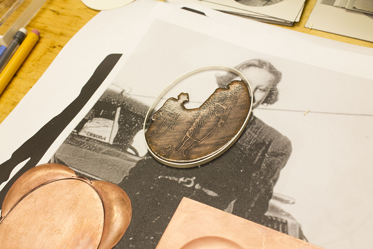 A brooch in progress with a photo of Barbara's mother in the background.
