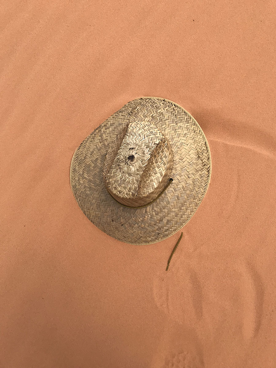 Sand holding my swept away hat for me!