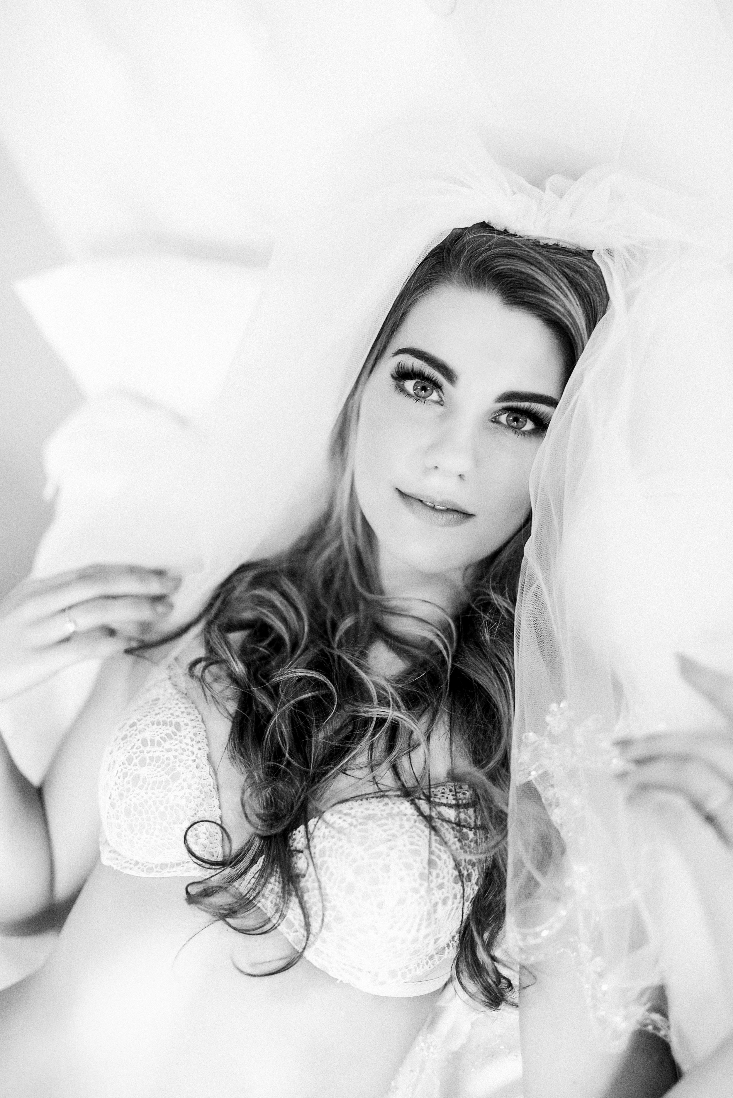 I had contacted Alex with the intentions to do a boudoir shoot with her as an anniversary gift for my husband. That was a HUGE deal because my insecurities tend to run my life. Alex was excited to meet and do a consultation to discuss the shoot so she can get why style you like, I'm a more modest type of person and she was all for it! While at the consultation she asked me why I was doing this shoot, so I told her. She was all for it as a gift, however she said it needed to be for me and not him. I sort of got where she was coming from and agreed. When it came time to do the shoot she had all of my favorite snacks, drinks, music and everything else you can think of! I sat there getting my hair and makeup done and picking out what to wear first. There were lots of laughs and stories exchanged. I was VERY nervous when it was time to start shooting. She was very reassuring and explained just what I needed to do and how to lose me. We talked and laughed throughout the whole thing. It was a truly liberating thing to have a whole day spent on ME, I never pamper myself, so I walked out feeling like a million bucks. Then came the revealing session. I think I was more nervous to see what they looked like than the actual shoot. We sat in her office and looked through the whole set of photos. I didn't say much, which was probably terrifying to her, but it was because I truly didn't know what to think or say. That was me, that's how my husband and friends and family see me when they tell me I'm beautiful. I had truly never loved a photo of myself before, and now all of a sudden I was looking at photo after photo where I felt beautiful and saw what everyone else saw. It was such a life changing experience, truly. I went from hating the beach because people could see me, to wanting to plaster my photos all over the place. For anyone who is even slightly considering a boudoir shoot, DO IT! And do it with Alex! Don't contemplate it, do it! It's a truly liberating and life changing 