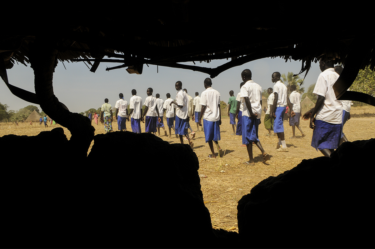 """Ariang school children march and sing in Dinka, """"The SPLA (Sudan People's Liberation Army) has tried through the gun to end the war, but the real peace will come from education."""" Gabriel Bol Deng, a former """"Lost Boy"""" who lives in Syracuse, has raised about $200,000 for Ariang, his home village. He decided to build a school when he saw children learning under trees. He also drilled six wells."""