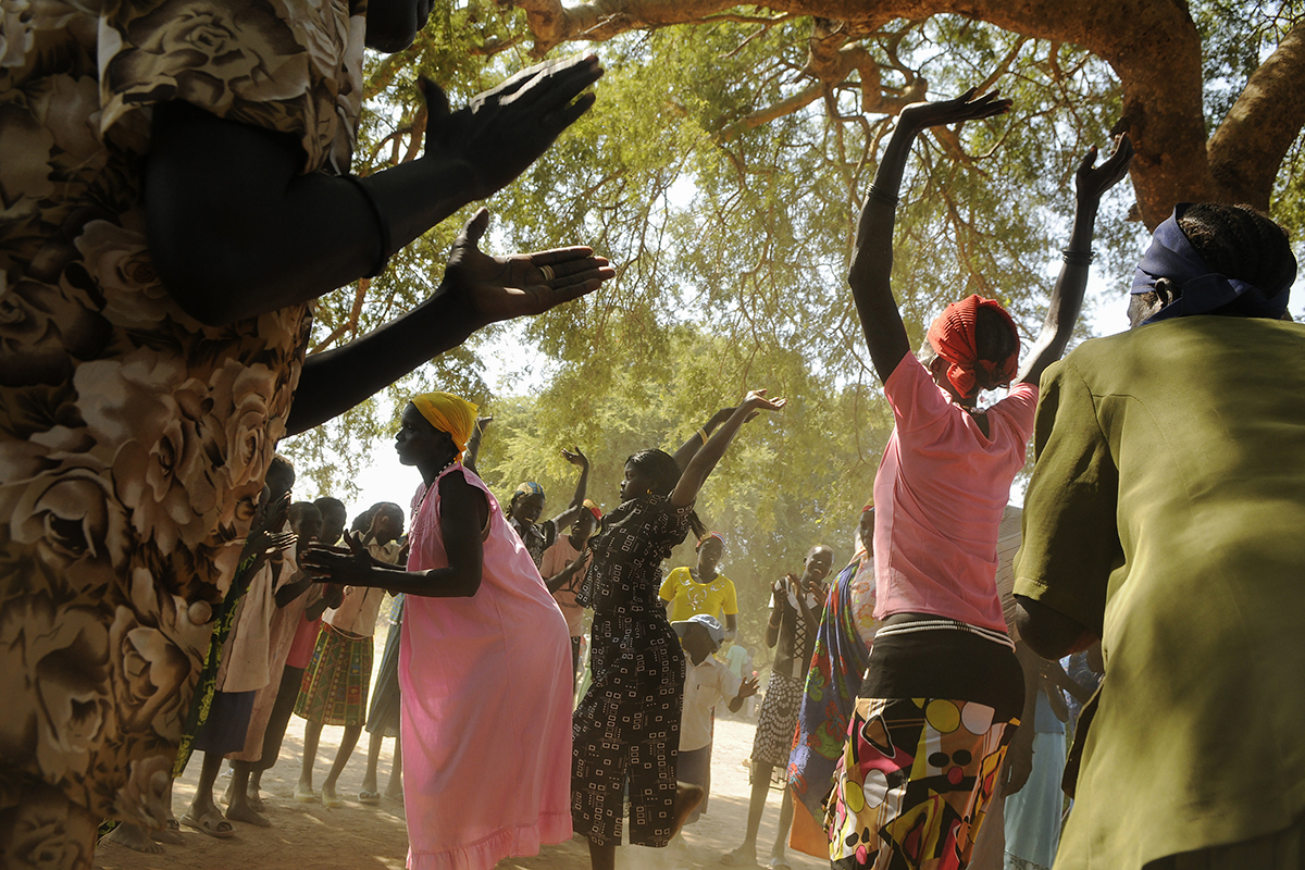 Women sing and dance as Gabriel Bol Deng, a former Lost Boy, visits Ariang, his home village, for the third time since fleeing the war in 1987. Gabriel, who settled in Syracuse, raised nearly $200,000 for Ariang to build a school and wells.