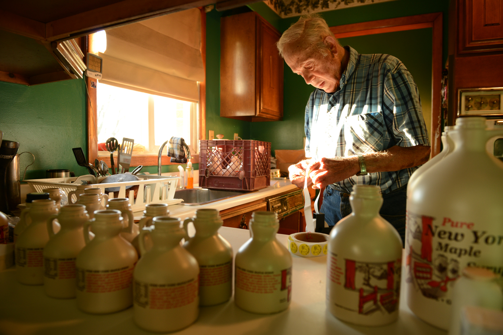 "Max bottles syrup in preparation for his upcoming trip to the Central New York Regional Market. Max and Esther, familiar faces at the market for decades, became friends with many of their customers. ""I've got to have something to do to take up my mind and the maple syrup has been the ideal thing for me."""