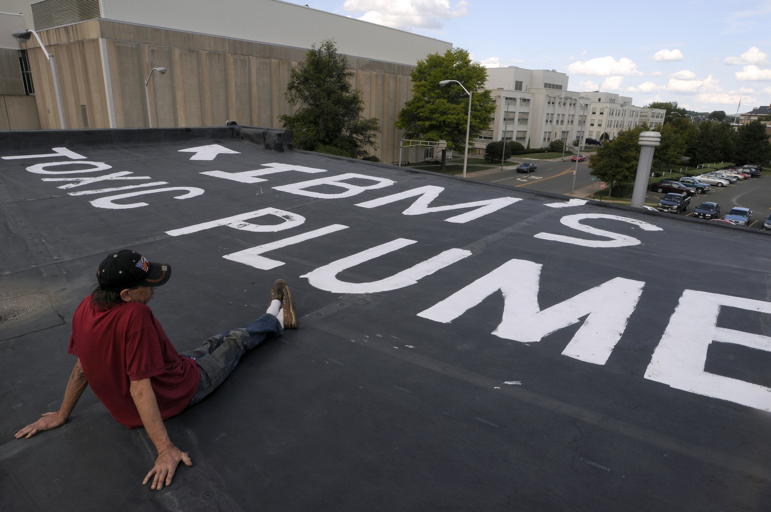 "Mark Bacon of Endicott, who lives across the street from the former IBM plant, painted the words ""IBM's Toxic Plume"" on his roof. Ray Baker, Bacon's neighbor, rests on the roof."