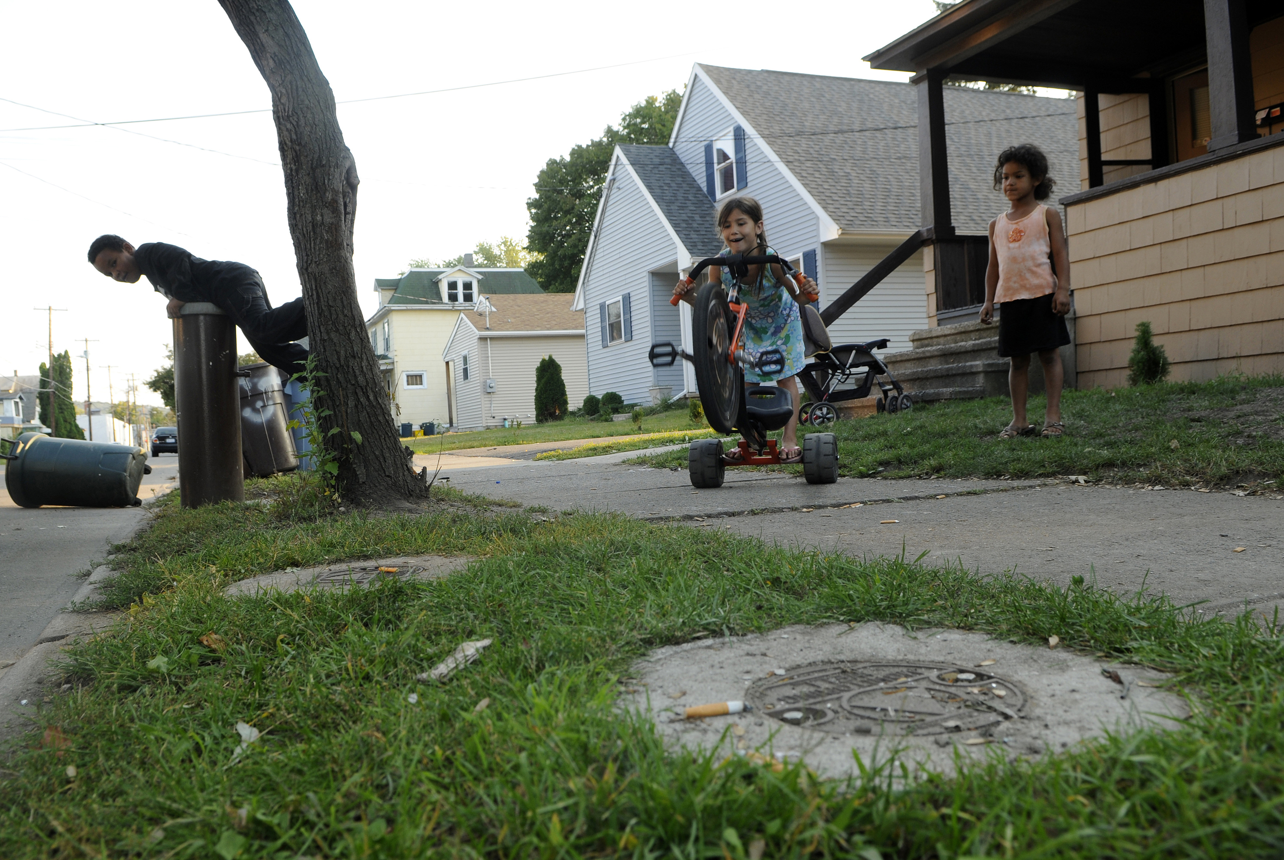 Analicia Morelock, 6, middle, her sister, Keke Haggerty, 5, right, and her neighbor, Andre Weather, 6, left, play in front of their Jackson Avenue home. In the foreground are monitoring wells that are regularly tested for TCE and other chemicals.