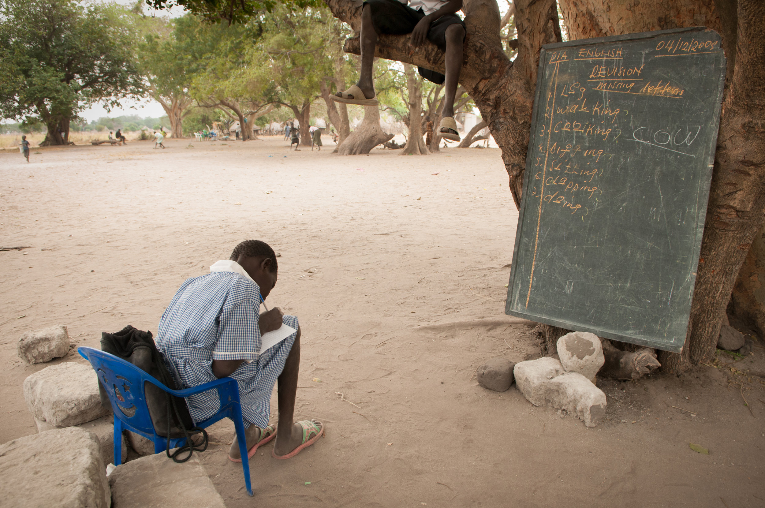 An elementary school student in Duk Payuel practices English as a classmate rests in the tree above.