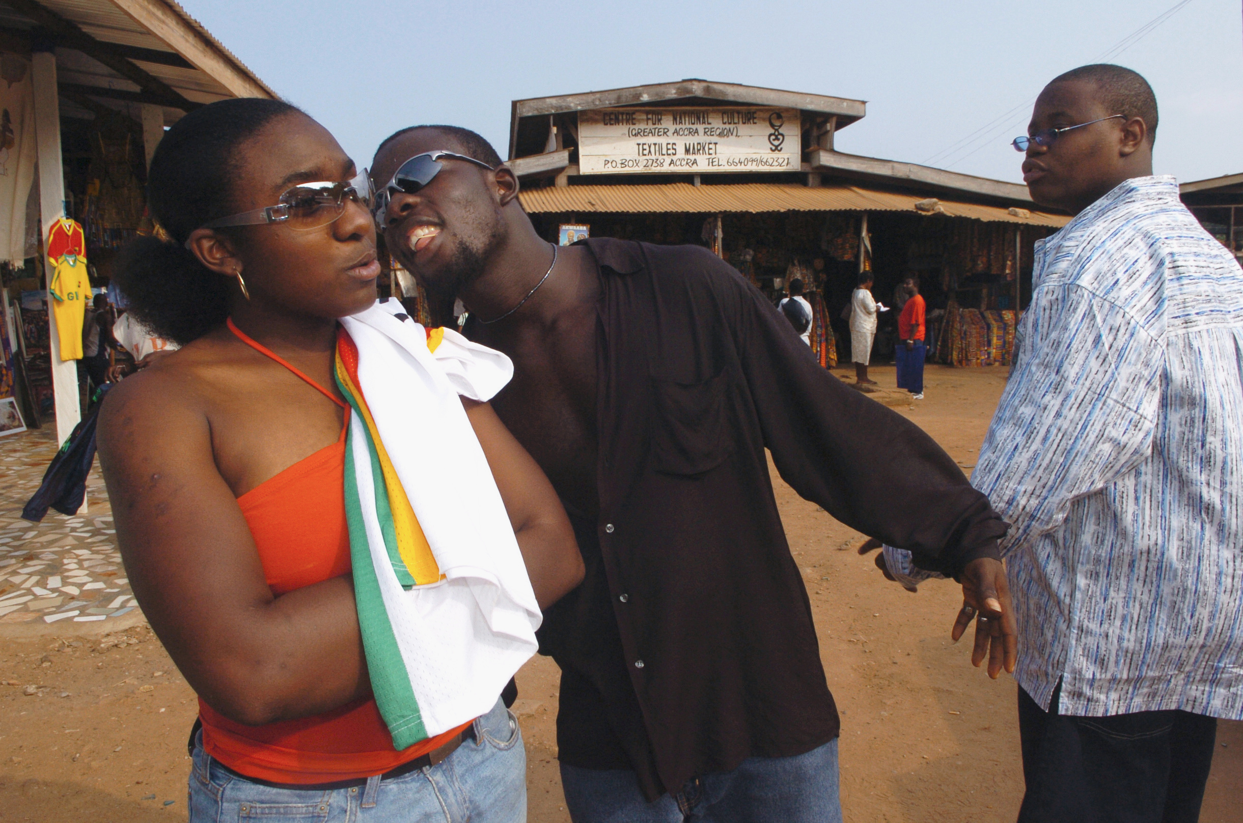 A merchant at the Arts Centre in Accra, middle, tries to sell Amanda Pruitt, 16, of Syracuse, a T-shirt as Le'Shem Escoffery (right) looks on. The teens were traveling with Africa Bound, a cultural education program.