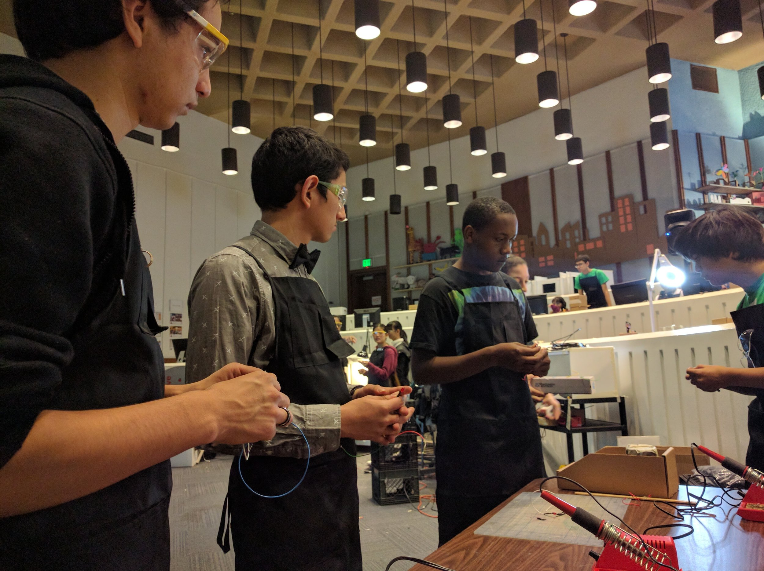 DJ, Javier and Thomas getting a soldering tutorial from Senior Intern Sebastian.