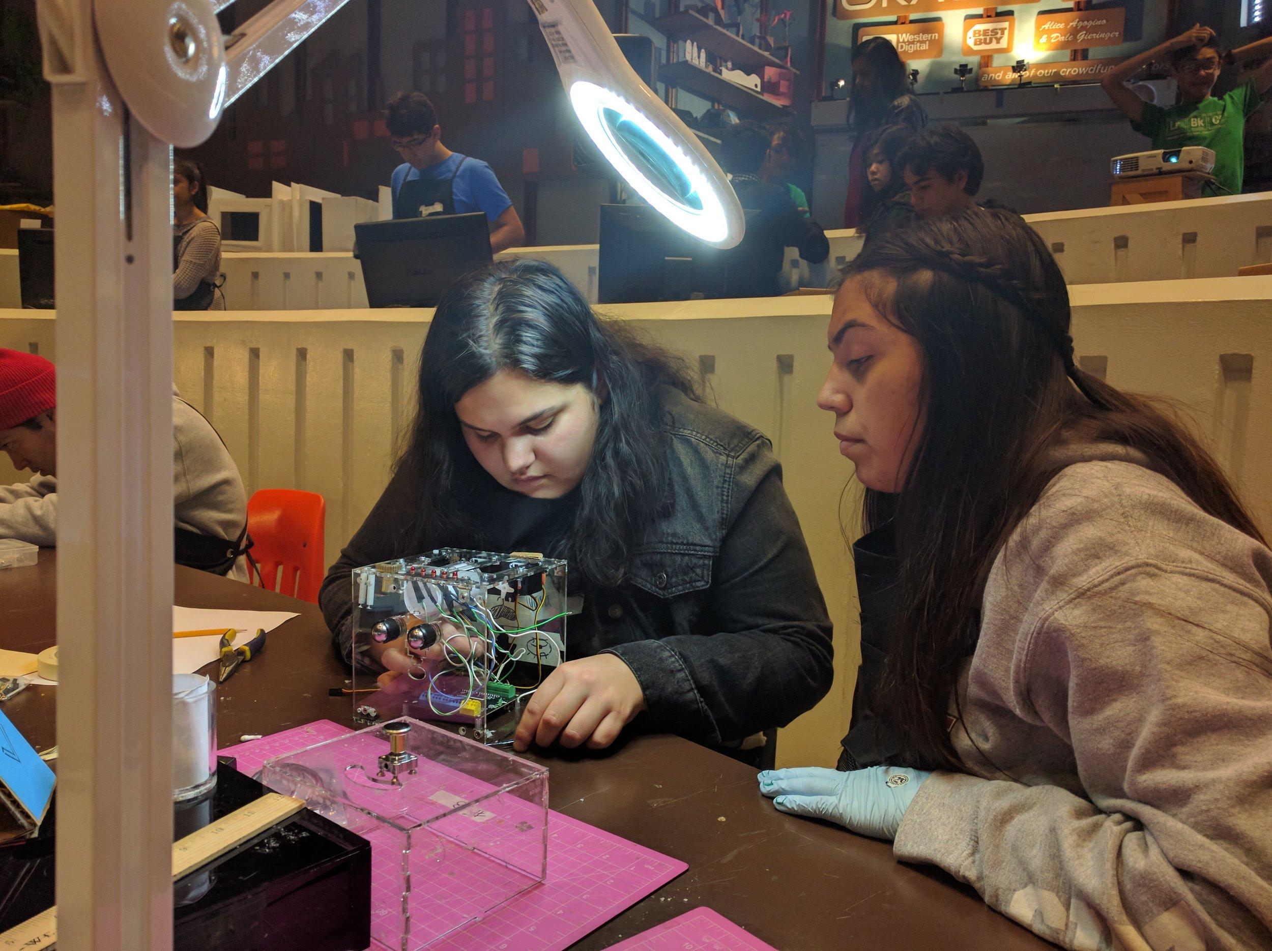 Alyssa and Jossalin working at wiring Jamie.