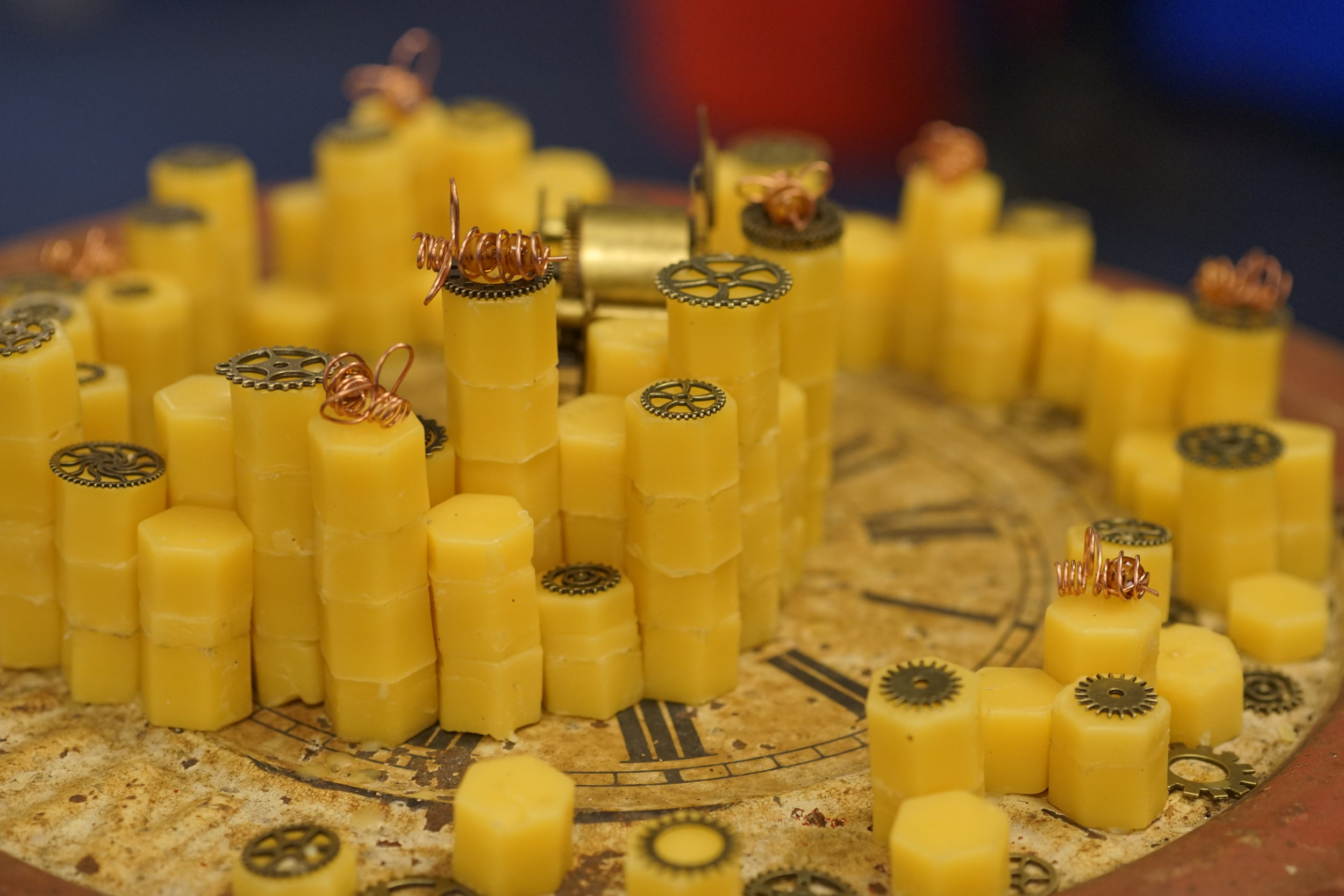 LAUREN NEVILLE - BEEHIVE COMPLEXITY THEORY   Sculpture.     Beehive Complexity Theory  combines an antique clock and old parts with honeycomb shaped stacks of beeswax. The piece uses small copper wire renderings of bees to talk about the similarities between complexity theory in beehives and mechanics.