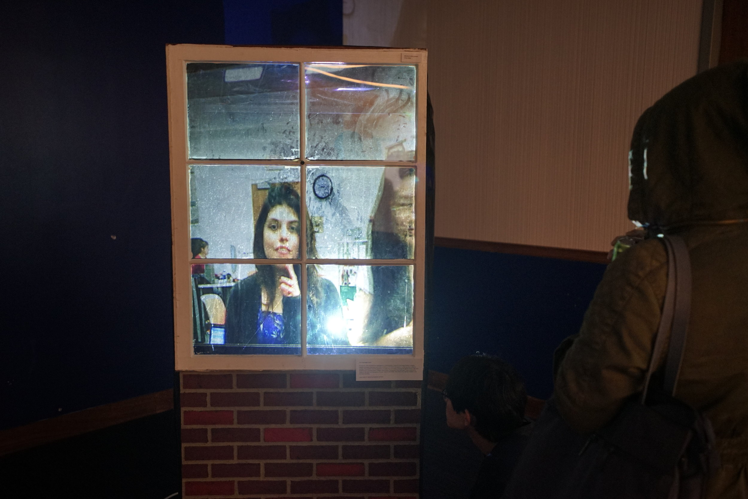 CHRIS MILLER - WINDOW TO THE PRESENT   Interactive installation.      Window to the Present  uses raspberry pi technology to record videos of everyone who looks into the prop window. However, when new individuals come up to the window, there is a time lag and participants will see the reflections of those before them and not themselves.
